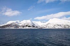 Opinião cênico da paisagem da viagem do barco em fiordes nevado bonitos no mar norueguês no céu azul e nas nuvens, Noruega Imagem de Stock Royalty Free