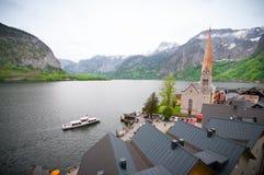A opinião cênico do imagem-cartão da aldeia da montanha famosa de Hallstatt com Hallstaetter considera nos cumes austríacos, regi Imagem de Stock