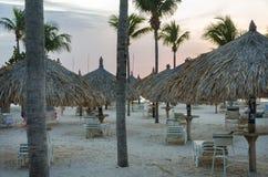 A opinião cênico do por do sol através dos hotéis cobre com sapê barracas Fotos de Stock