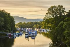 A opinião cênico do por do sol do porto de Balloch perto de Loch Lomond com barcos de flutuação refletiu no rio Leven, Escócia, R imagem de stock