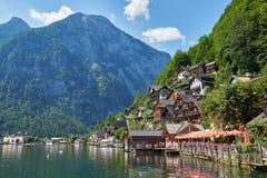 Opinião clássica do cartão da cidade famosa da beira do lago de Hallstatt que reflete no lago Hallstattersee nos cumes austríacos imagem de stock