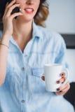Opinião colhida do tiro a jovem mulher que fala em um telefone celular com o copo em sua mão Foto de Stock