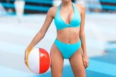opinião colhida a mulher no roupa de banho que levanta com a bola de praia inflável imagem de stock royalty free