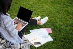 Opinião colhida o estudante fêmea que datilografa no portátil, sentando-se em gras Fotografia de Stock Royalty Free