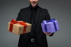 Opinião colhida o homem no terno preto que mantém duas caixas de presente isoladas no conceito do dia das mulheres cinzentas, int Fotos de Stock