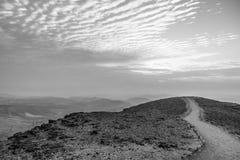 A opinião colorida branca e preta da paisagem na terra judean do deserto com o céu mágico no fundo e na cor nubla-se Imagem de Stock Royalty Free