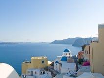 Opinião com as cúpulas famosas da igreja, Santorini do mar, Grécia imagem de stock royalty free