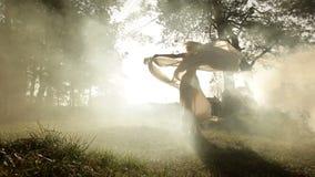 Opinião completo a mulher encantador que dança e que balança circularmente com o xaile na névoa Lugar da floresta video estoque