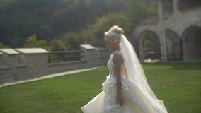 Opinião completo a noiva loura atrativa do th no vestido de casamento à moda longo que corre ao longo do jardim durante o por do  filme