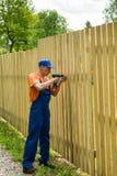 Opinião completo o carpinteiro que fixa a cerca de madeira Imagem de Stock Royalty Free