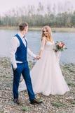 Opinião completo os recém-casados que guardam as mãos ao andar ao longo da praia imagens de stock