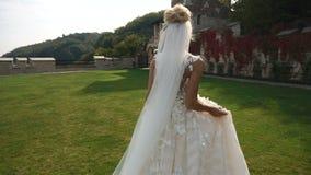 Opinião completo traseira a noiva loura encantador nova no vestido longo bonito que corre ao longo do jardim de florescência filme