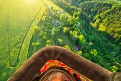 Opinião da cesta do balão de ar quente, voando acima do campo rural Fotografia de Stock Royalty Free
