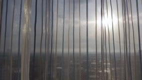 Opinião da cidade através da cortina transparente Foto de Stock