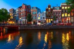 Opinião da cidade da noite do canal de Amsterdão com casas holandesas Imagem de Stock Royalty Free