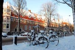 Opinião da cidade do por do sol de Amsterdão no inverno com bicicletas estacionadas Fotos de Stock Royalty Free