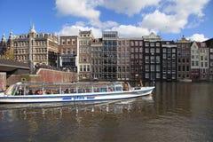 Opinião da cidade dos canais, de casas holandesas e de barco da excursão, Amsterdão, Neth imagem de stock
