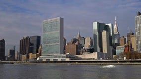 Opinião da construção da sede de United Nations de Roosevelt Island durante o dia ensolarado da queda em East River em New York C video estoque