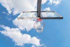 A opinião da consulta da borda da aro de basquetebol e o encosto nublam-se o céu azul Imagem de Stock