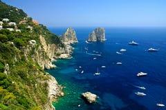 Opinião da costa de Capri com rochas de Faraglioni e barcos, Itália foto de stock royalty free