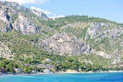 A opinião da luz do dia às construções aproxima o litoral, árvores verdes e o ro grande fotos de stock royalty free