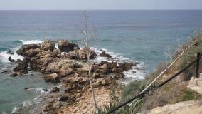 Opinião da manhã na praia rochosa As ondas do mar Mediterrâneo deixam de funcionar nas pedras que criam a espuma e as bolhas bran filme