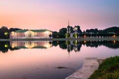 Opinião da noite através da lagoa no palácio e na igreja com a torre de sino na museu-propriedade Kuskovo, Moscou Foto de Stock
