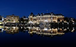 A opinião da noite da cidade de Victoria, construções é refletida na água imagens de stock