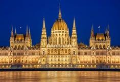Opinião da noite da construção húngara do parlamento no banco do Danúbio em Budapest, Hungria Imagens de Stock