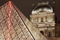 Opinião da noite da pirâmide e do museu do Louvre em Paris Foto de Stock