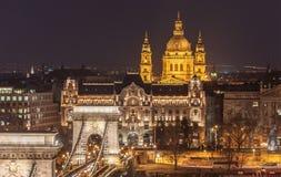 Opinião da noite da ponte Chain de Szechenyi e da igreja St Stephen & x27; s em Budapest Imagens de Stock