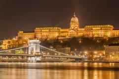 Opinião da noite da ponte Chain de Szechenyi sobre Danube River e Royal Palace em Budapest, Fotografia de Stock Royalty Free