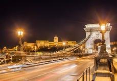 Opinião da noite da ponte Chain de Szechenyi sobre Danube River e Royal Palace em Budapest Fotos de Stock Royalty Free