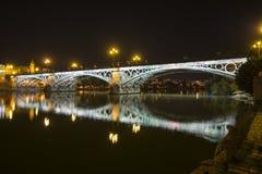 Opinião da noite da ponte de Triana em Sevilha, Espanha foto de stock royalty free