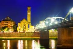 Opinião da noite da ponte sobre Ebro River e igreja em Tortosa Foto de Stock