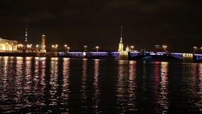 Opinião da noite da terraplenagem da universidade de St Petersburg através da fortaleza do rio Peter e do Paul de Neva, ponte do  filme