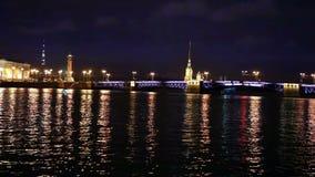 Opinião da noite da terraplenagem da universidade de St Petersburg através ponte do palácio da fortaleza do rio Peter e do Paul d video estoque