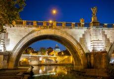 Opinião da noite de Ponte Sant Angelo, de Angel Bridge santamente, e de Tibre em Roma, Itália foto de stock