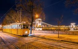 Opinião da noite do bonde no fundo da ponte Chain em Budapest Fotos de Stock Royalty Free