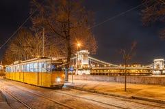 Opinião da noite do bonde no fundo da ponte Chain em Budapest, Hungria Imagem de Stock Royalty Free