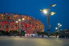 A opinião da noite do ninho do pássaro da vila dos Olympics no Pequim, China imagem de stock