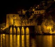 A opinião da noite do porto de pedra antigo do navio, castelo, paredes com luzes refletiu ao mar e atrás dela casas velhas Alanya Fotografia de Stock Royalty Free