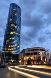 Opinião da noite do prédio de escritórios da torre do céu com as auto fugas claras Fotos de Stock Royalty Free