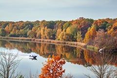 Opinião da paisagem do outono da queda na multi floresta colorida do outono que reflete na condução da água e do barco Imagem de Stock Royalty Free