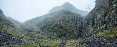 Opinião da paisagem do panorama ao longo da passagem de montanha rochosa nevoenta em Autum Fotos de Stock Royalty Free