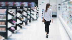 A opinião da parte traseira, compra da menina nos cosméticos compra, vai entre prateleiras, movimento lento