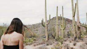 Opinião da parte traseira do movimento lento a mulher atrativa nova do turista no vestido longo que anda no parque nacional do de video estoque
