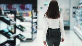 A opinião da parte traseira, mulher vai à loja ao longo das prateleiras, movimento lento dos cosméticos