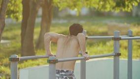 Opinião da parte traseira o homem da aptidão que faz exercícios em barras no campo atlético vídeos de arquivo