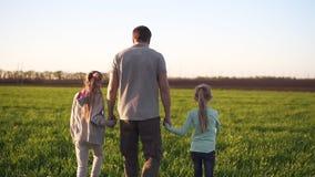Opinião da parte traseira um pai forte, novo que anda por um prado verde com as duas filhas pequenas Guardando os com mãos filme